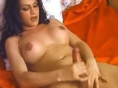 Bewitching shemale enjoys masturbating solo on red bed